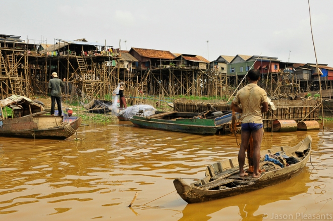 1) fisherman on river in front of houses